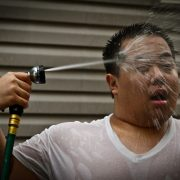 Man spraying himself with water hose