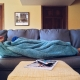 Cold person laying on the couch under a blanket.